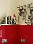 Küchengeräte an Stange und auf Bord in Edelstahl über kräftig roter Glasplatte mit integrierten Steckdosen