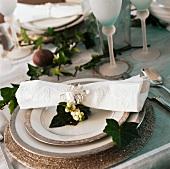 Silbernes Efeublatt an bestickter Leinenserviette auf Tellern mit feinem, silbergrauem Rand als festliches Weihnachtsgedeck