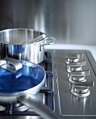 Pfanne mit blauem Deckel und ein Topf aus Edelstahl auf einem Gasherd mit Edelstahl-Bedienknöpfen