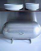 Brotkasten aus Edelstahl unter einem Holzregal mit weissen Tellern