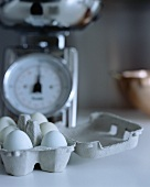 Eiern im Eierkarton vor einer Küchenwaage