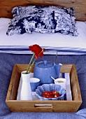 Holztablett mit blauer Teekanne und Tassen auf einem Bett mit blau-weisser Bettwäsche