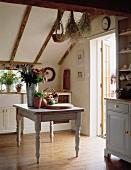 Alter, grau lackierter Holztisch mit Früchten und Blumen in Landhausküche mit Dachschräge und Holzboden