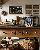 Verschiedene Küchenutensilien auf einem antiken Holztisch mit Schublade