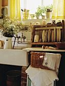Kiefer Tellerhalter und Korb neben weißem Keramikwaschbecken in der landhausküche
