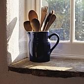 Ein blauer Keramikkrug mit Holzgeschirr steht auf einer Fensterbank