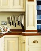 Sammlung moderner Messer an Magnetschiene in cremefarbener Landhausküche