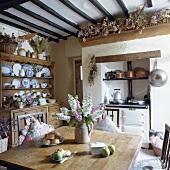 Ländliche Wohnküche mit Anrichte aus Kiefernholz und mit altem Ofen