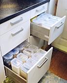 Offene Schubladen eines Küchenunterschrankes mit Aufbewahrungsboxen
