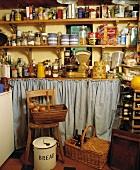 Alte Speisekammer mit Vorratsdosen in Holzregalen und Körben mit Lebensmitteln
