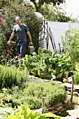 A man with a watering can in a vegetable garden