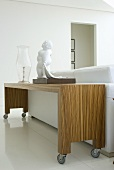 Eine Skulptur und eine Glasvase auf einem Ablagetisch auf Rollen hinter dem Sofa