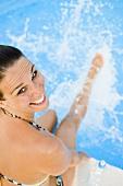 Frau sitzt am Schwimmbecken