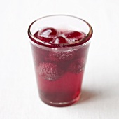 A glass of red lemonade with raspberries and cherries