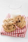 Cookies und Glas Milch auf kariertem Tuch