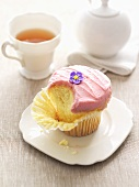 Partly-eaten cupcake with buttercream & sugar flower, tea