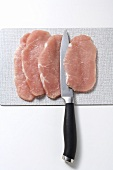 Four pork escalopes with knife on board