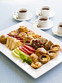 Platter of savoury pastries and fruit for breakfast, tea