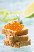 Salmon caviar on tiny slices of bread