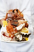 Chef holding platter of assorted seafood