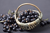 Blackcurrants in and beside a small wicker basket