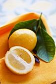 Whole lemon and half a lemon with leaves