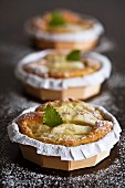 Three small apple tarts with icing sugar and mint