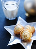 Quark pastry pinwheels on star-shaped silver plate, glass of milk