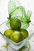 Four limes with net bag in glass dish
