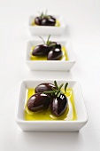 Black olives with olive oil and rosemary in small dishes