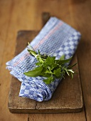 A small bouquet of herbs on a kitchen towel and a wooden board