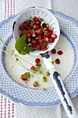 Woodland strawberries in an enamel straining spoon and on a plate