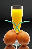 Tangerines with straws in front of a glass of juice