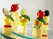 Cubes of cheese on sticks with basil, vegetables and grapes