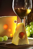 Emmental cheese, a glass of white wine and grapes