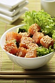 Diced salmon with sesame on a bed of salad (Asia)