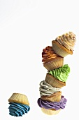 A stack of cupcakes decorated with coloured cream