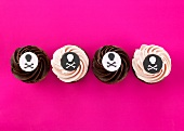 Four cupcakes with pirate decoration