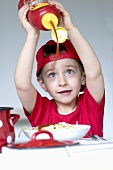 A little boy squirting ketchup onto spaghetti