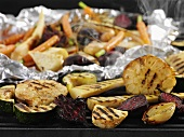 Root vegetables and garlic on a grill