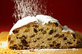Raisin stollen being dusted with icing sugar