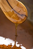 Honey & sugar caramel drizzling from a wooden spoon