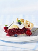 A piece of cherry pie with fresh cherry and blueberries