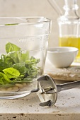 Basil leaves and pine nuts in a measuring cup