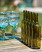 Empty glasses and bottles on a garden table