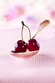 A pair of cherries on a spoon