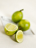 Two whole limes and one cut open