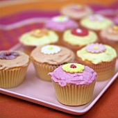Several colourful cup-cakes decorated with sugar flowers