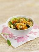 Garnelencurry mit Gemüse und Basilikum in einem Schälchen