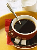A cup of black coffee with milk and water
